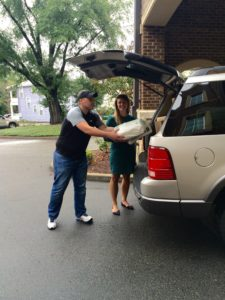 Staff loading cars to transport the first shipment of diapers from the Diaper Bank to the Catholic Charities office.