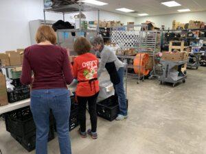 Volunteers work to pack boxes of food.