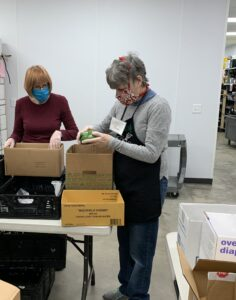 Suzan Perry volunteers during her shift at the Durham Community Food Pantry placing a vegetable into a box.