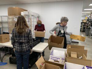 Volunteers pack food into boxes.